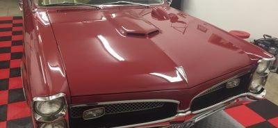 hood shot classic car on garage tile parking pad