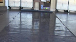 Rippled garage floor mat that will not lay flat